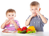 Boys and plates of vegetables and meat — Stock Photo