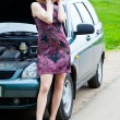 A woman is calling on a phone near the broken car — Foto de Stock