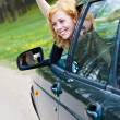 A smiling woman in a car is wagging — Stockfoto