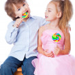 Boy and girl with lollipops - Stock Photo