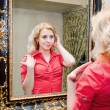 Reflection of young woman in a mirror - Stock Photo