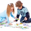 Boy and girl are playing with puzzle — Stock Photo #6010396