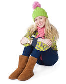 A beautiful girl in a funny cap is sitting on a floor — Stock Photo