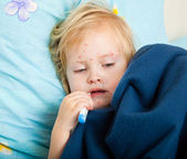 A sick girl is measuring the temperature — Stock Photo