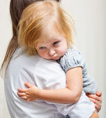 A mother is holding a sick girl. — Stock Photo