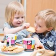 Stock Photo: Funny children are eating dessert