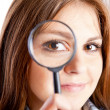 Girl is looking through magnifying glass - Stok fotoğraf