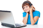 Red-haired teen-girl listen to music in headphones with laptop — Stock Photo