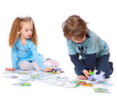 Boy and girl are playing with puzzle — Stock Photo