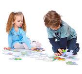 Niño y niña están jugando con rompecabezas — Foto de Stock