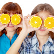Two girls are looking through oranges — Stock Photo #6267840