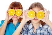 Two girls are looking through oranges — Foto Stock