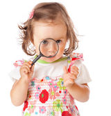 A little girl is looking through the loupe — Stock Photo