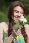 Laughing young woman with flower — Stock Photo