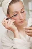 Woman in bathrobe putting mascara — Stock Photo