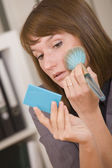 Woman applying make up in office — Stock Photo