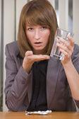 Stressed businesswoman taking pills — Stock Photo