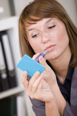 Woman putting on makeup by office work — Stockfoto