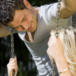 Romantic couple talking on a swing — Stock Photo