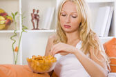 Sad woman eating snacks at home — Stock Photo