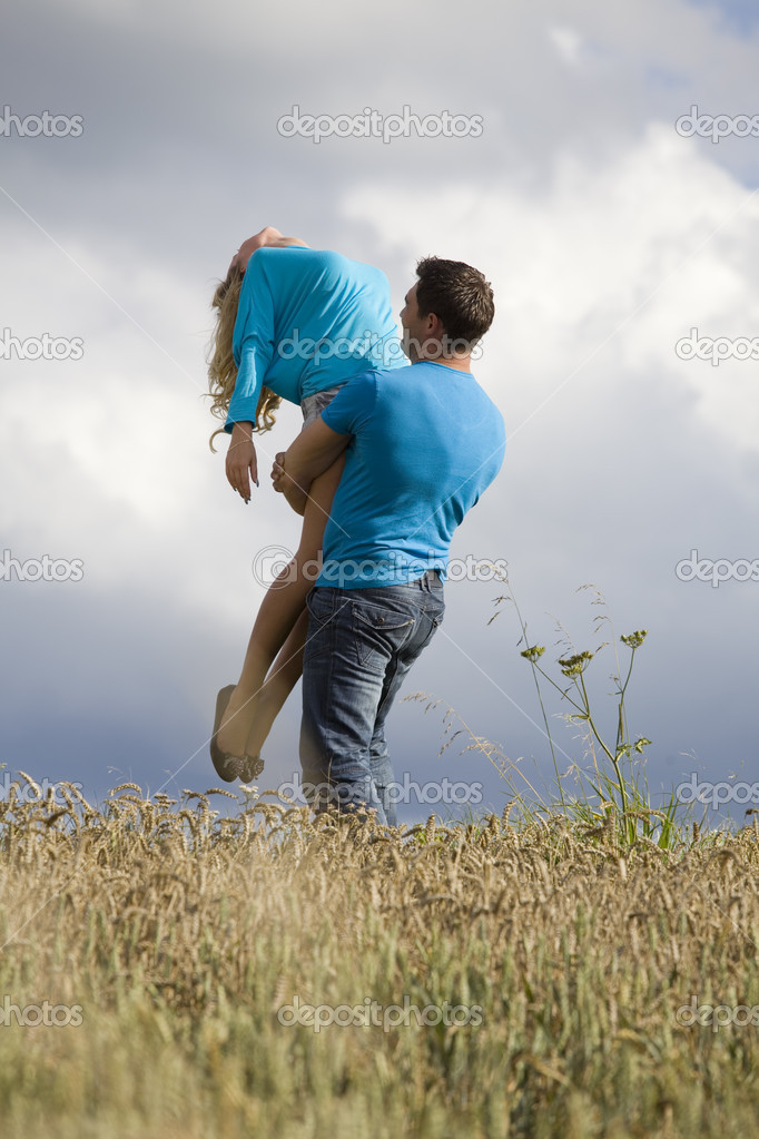 Man holding woman up in air in countryside  Stock Photo #6421343