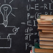 Light bulb drawn on blackboard and books — Stock Photo