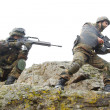 Soldiers moving on mountain with guns — Stock Photo