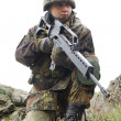 Soldier with automatic gun covering — Stock Photo