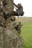 Armed military alpinist climbing — Stock Photo