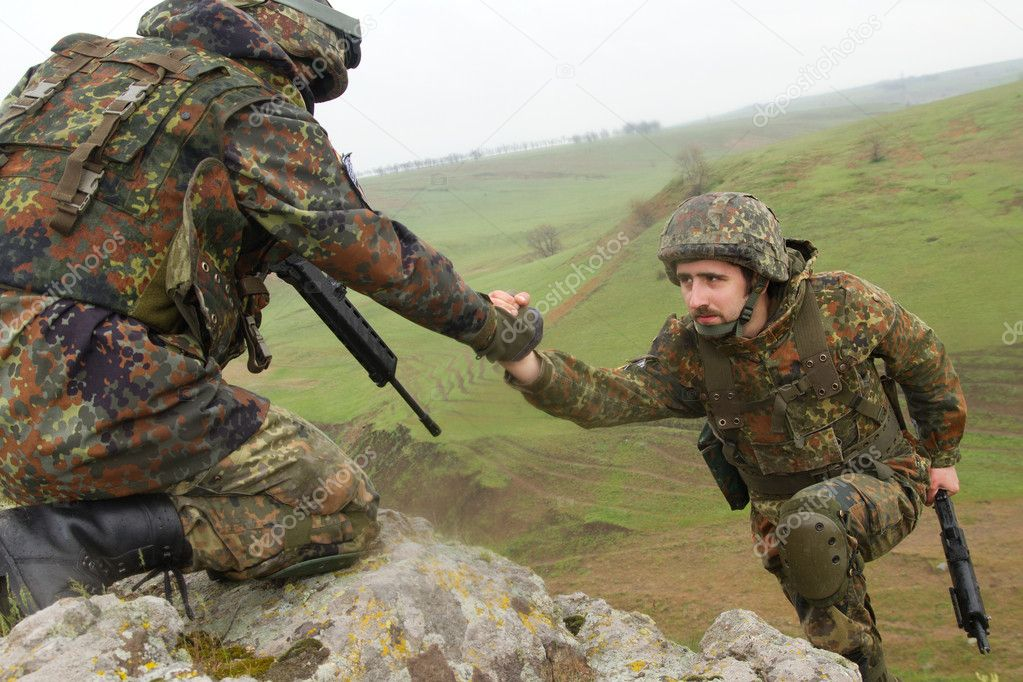 Military man helping his friend to climb up the rock  Stock Photo #5607453