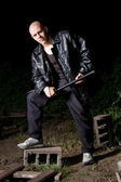 Bald thug armed with baton outdoors at night — Stock Photo