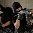 Soldiers in black masks with weapons - Stock Photo