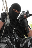 Soldier in black mask hanging on rope with Ak-47 rifle — Stock Photo