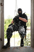 Soldier in black mask wntering the window on rope — Stock Photo