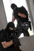 Soldiers in masks entering the window with Ak-47 rifles — Stock Photo