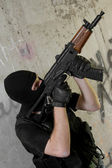 Soldier in black mask moving upstairs with AK-47 rifle — Stock Photo