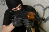 Soldier in black mask targeting with AK-47 rifle — Stock Photo