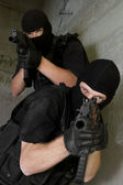 Soldiers in black masks targeting with AK-47 rifles — Stock Photo