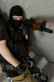 Soldier in black mask recharging AK-47 rifle — Stock Photo