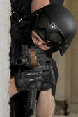 Soldier in black mask targeting with AK-47 rifle from cover — Stock Photo