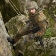 Royalty-Free Stock Photo: Armed soldier hanging on a cliff