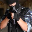 Stock Photo: Armed soldier in black mask targeting with a gun