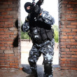 Armed soldier in black mask targeting with a gun - Stock Photo