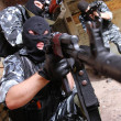 Soldiers in black masks targeting with guns - Stock Photo