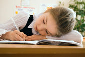 Schoolgirl writing in the exercise book — Stock Photo