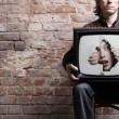 TV with a picture of the girl -facing through a hole in the hands of a seat — Stock Photo