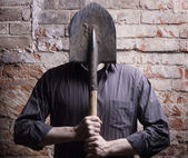 A man hides his face behind a shovel. — Stock Photo