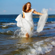 Bride running in waves — Stock Photo