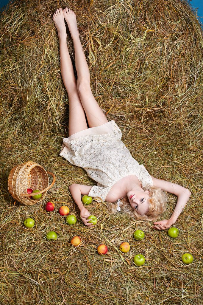 Portrait of beautiful blonde country girl posing laying on yellow hay with apples spilled from basket  Stock Photo #5714449