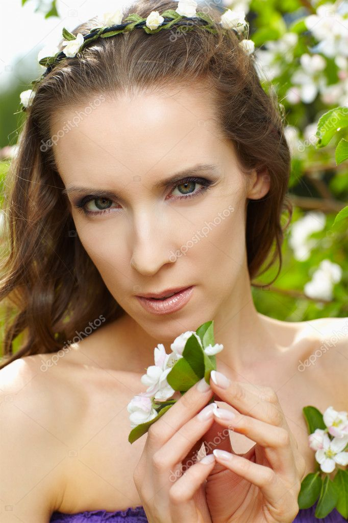 Outdoor portrait of beautiful woman with fresh skin posing in garland near blooming apple tree — Stock Photo #5850344